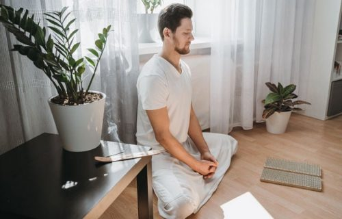 samadhi-retreat-centre-young-man-meditating-on-his-living-room-on-the-floor-sitting-in-the-lotus-position-with-closed-eyes_t20_Xvwnm6